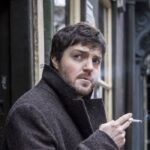 Tom Burke è Cormoran Strike in Strike serie tv Credits Warner Bros. Entertainment, Inc e Mediaset