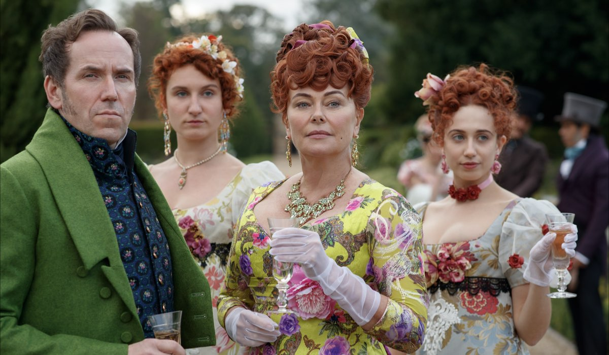 Bridgerton albero genealogico. Famiglia Featherington. Da sinistra: Lord Featherington (Ben Miller), Prudence (Bessie Carter), Lady Portia (Polly Walker), e Philippa (Harriet Cains) in una scena di Bridgerton. Credits: Liam Daniel/Netflix.